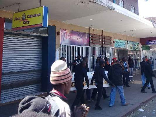 59ae7c818eb7f - Photos: Family place body of their son at the front of his killer's shop in Zimbabwe