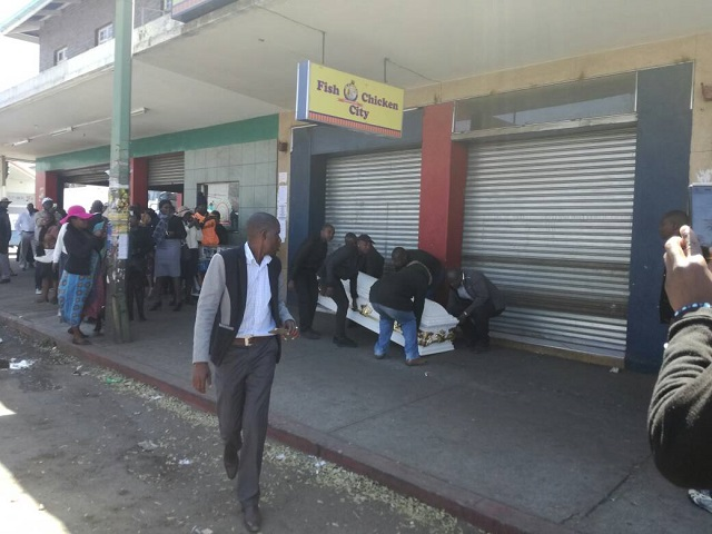 59ae7d1f18d1e - Photos: Family place body of their son at the front of his killer's shop in Zimbabwe