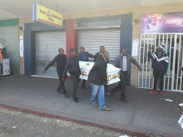 59ae7e65dc70e - Photos: Family place body of their son at the front of his killer's shop in Zimbabwe