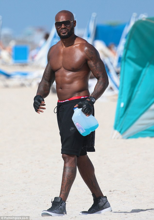 Shirtless Tyson Beckford shows off his sculpted six-pack while working out on the beach