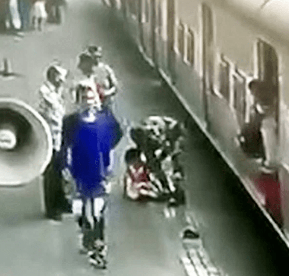 Girl, 5, saved at last second by stranger after slipping out of mum?s hand and falling under moving train (video)