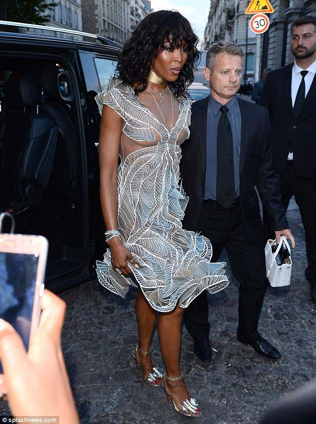 Naomi Campbell, 48, goes braless in plunging sheer dress to star-studded Vogue party in Paris (Photos)