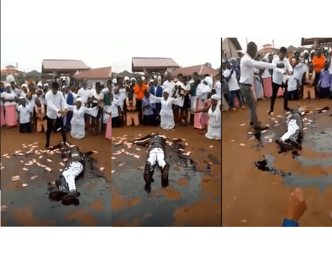 Pastor causes a stir as he rolls in engine oil, while members spray money on him during church crusade (Video)