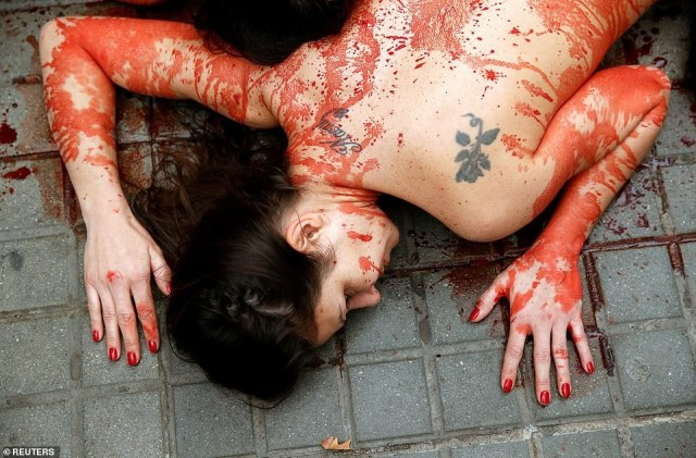 Animal rights activists go naked and smear fake blood on themselves to protest animal cruelty (photos)