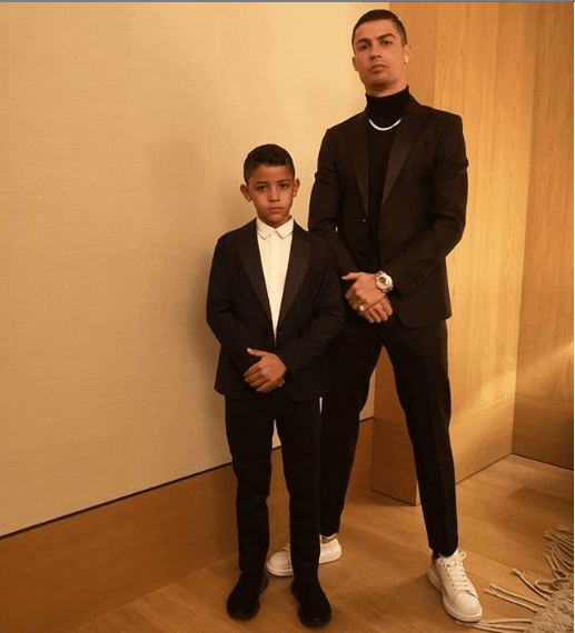 Like father like son! Cristiano Ronaldo and his son strike a pose in matching suits (Photo)
