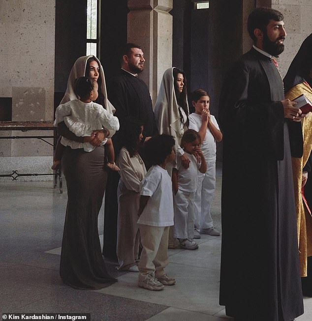 Kim Kardashian wears traditional headscarf and figure-hugging dress as she gets baptized with her children in Armenia (Photos)