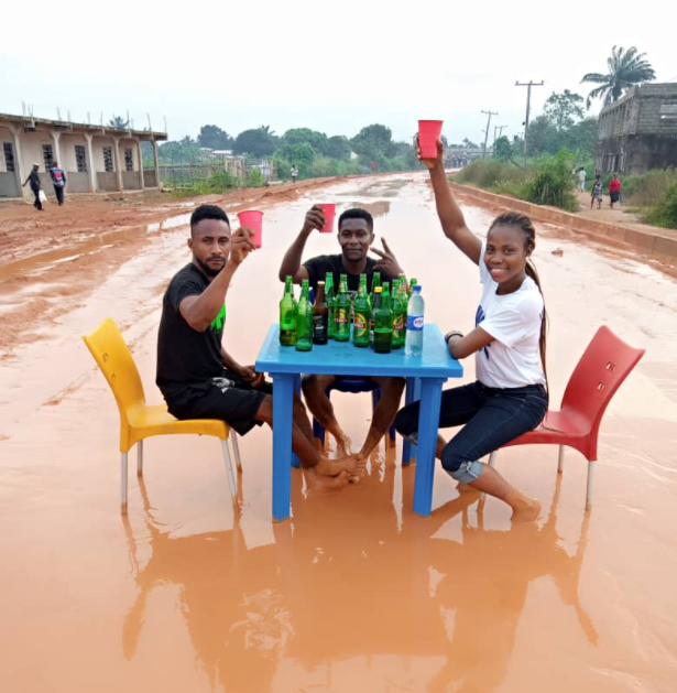 Friends drink beer on a bad road in Owerri to draw attention to the state of the road