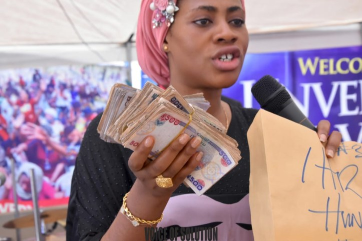 Prophetess Rose supports a pastor and a soldier with cash at Unveiling City Abuja