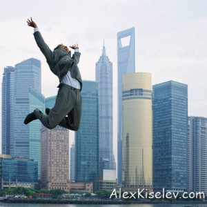 Shanghai, China --- Mixed race businessman jumping in air --- Image by © Dave and Les Jacobs/Blend Images/Corbis