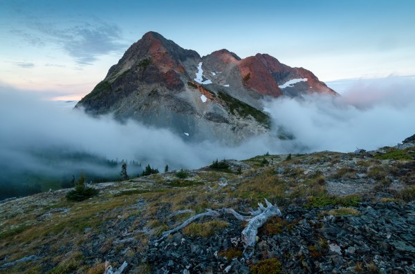 First light of sunrise hits the peak of Coquihalla mountain while fog surrounds the lower mountain.