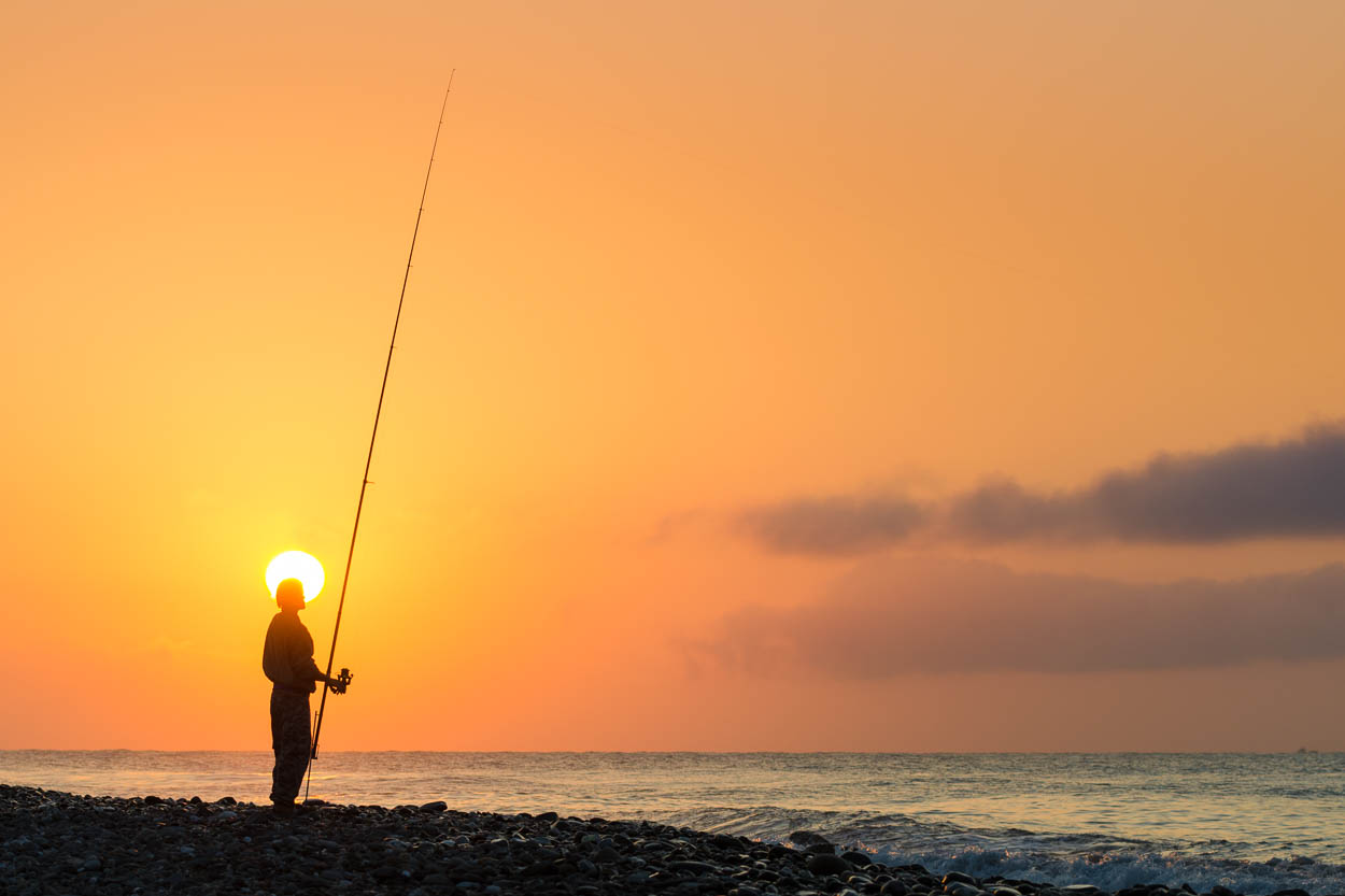 A fisherman is haloed by the rising sun