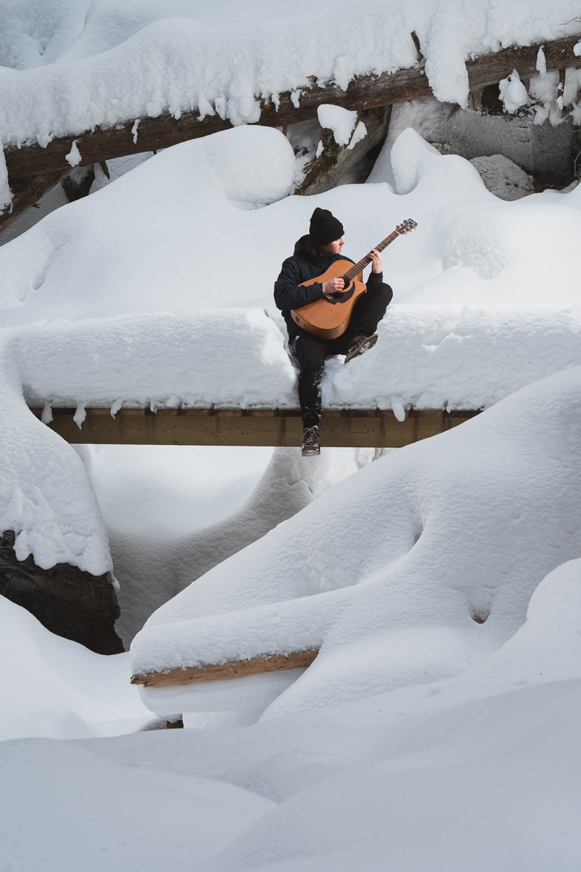 A musician plays guitar in the snow of Jamieson Creek
