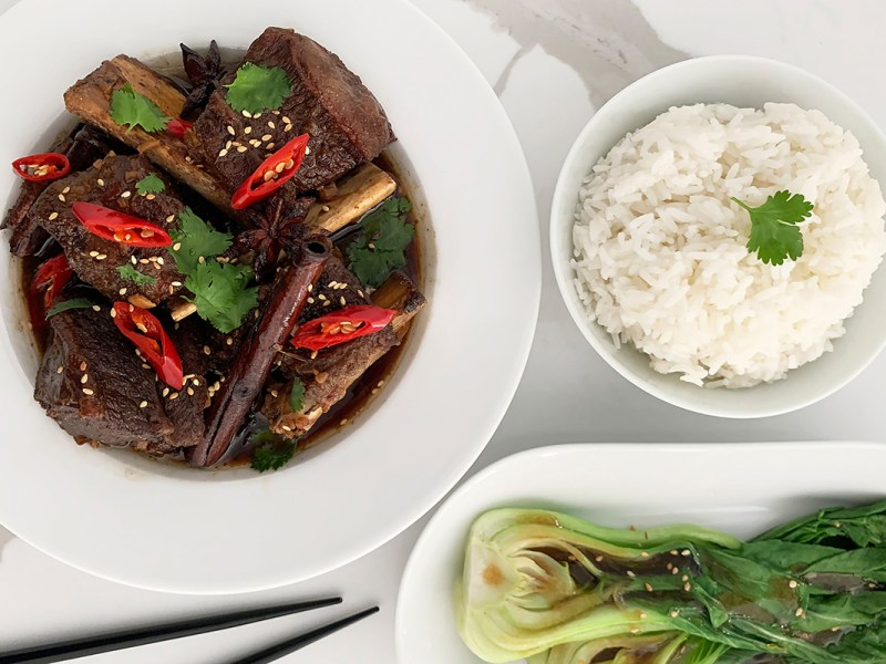 A bowl of Asian braised beef short ribs served with asian greens and rice