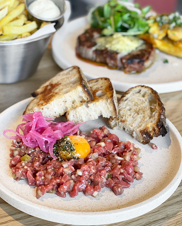A plate of steak tartare served with egg yolk, pickled peppers and toast from Besk