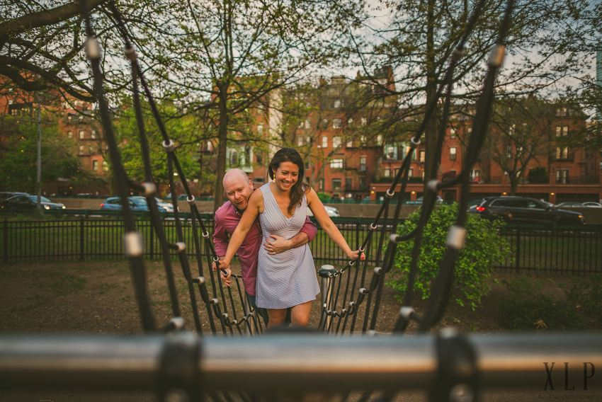 couple climbing jungle gym during engagement session
