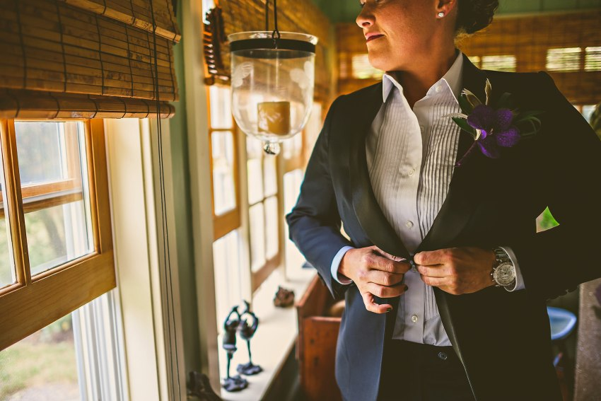 moody portrait of bride in tux by window
