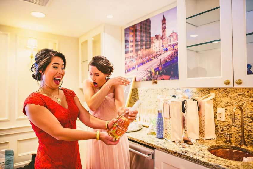 bride and bridesmaid opening champagne bottle