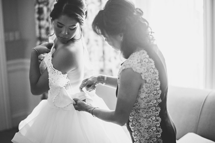bride putting on dress with mother