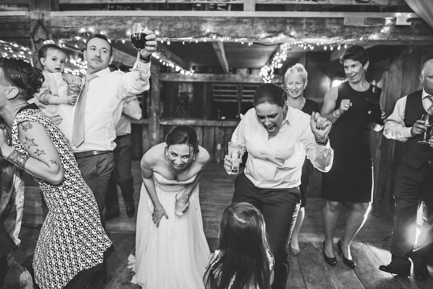 same sex brides dancing with flower girl at wedding reception