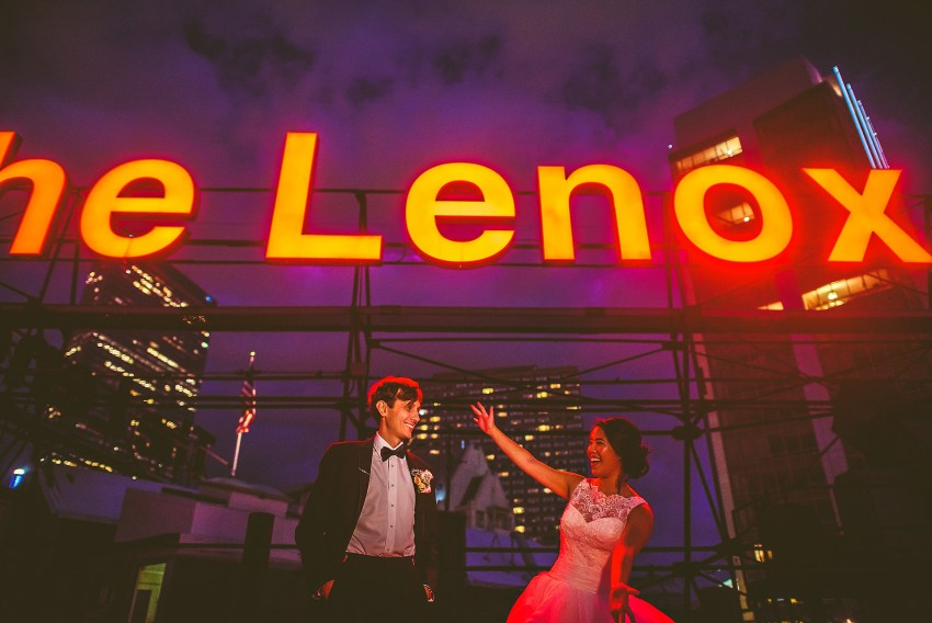 bride and groom in front of lenox sign