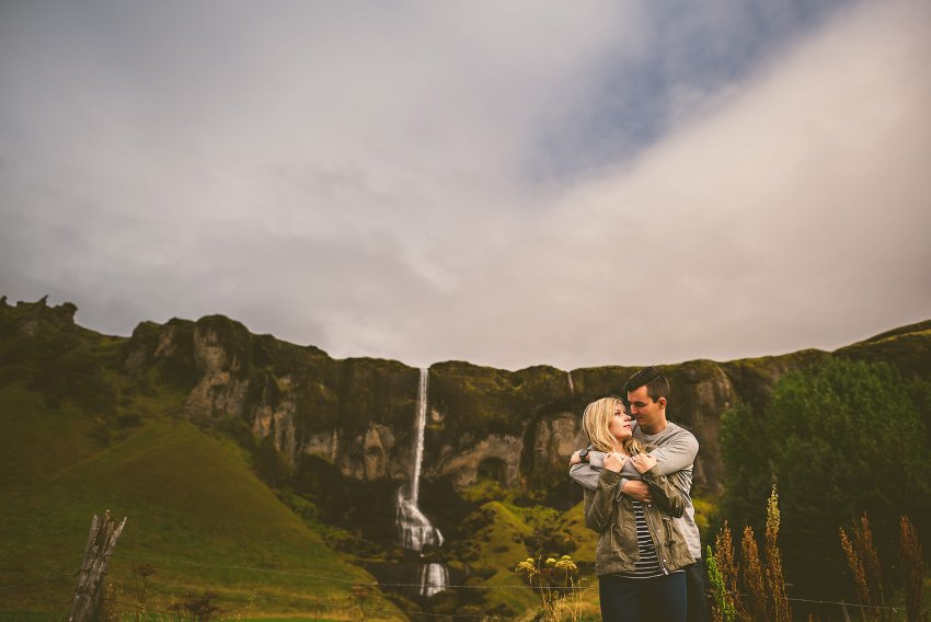 Couple hugging by waterfall in Iceland