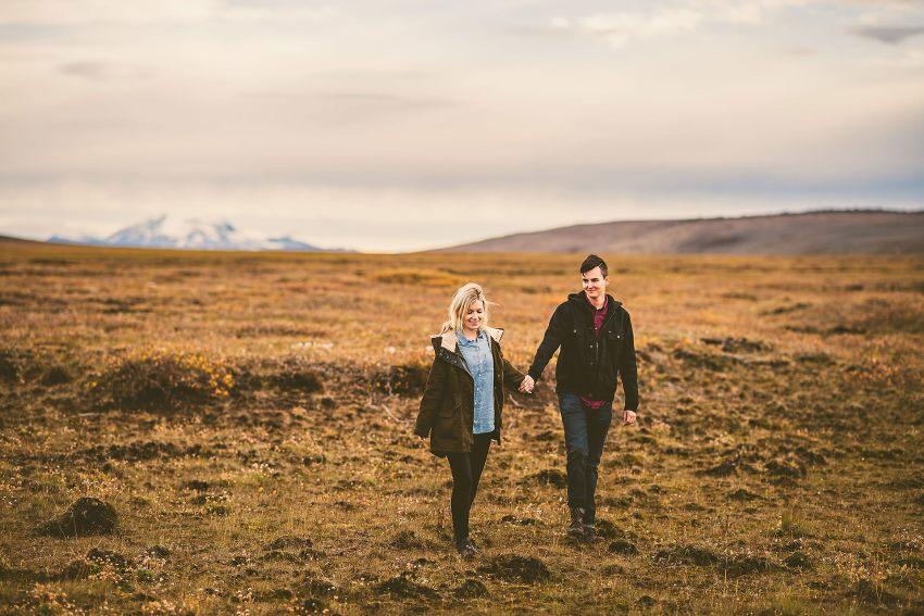 couple walking across Icelandic terrain