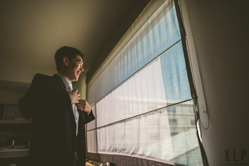 Groom portrait by window