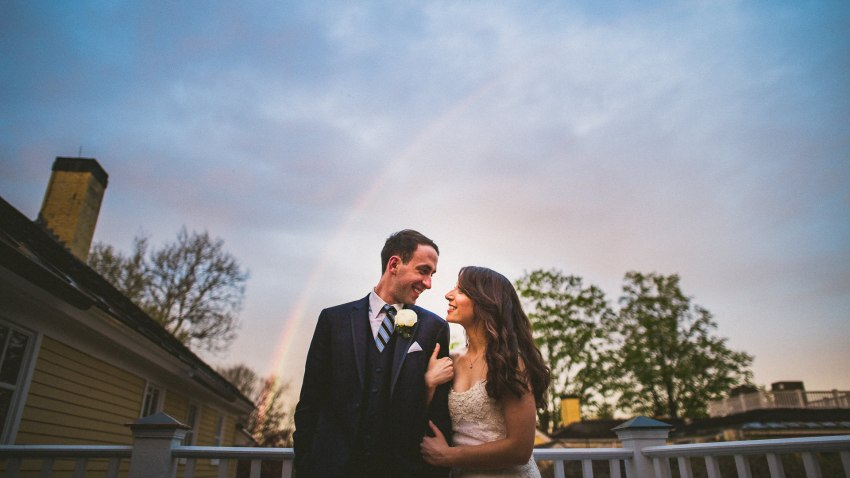 Dramatic wedding portrait with rainbow