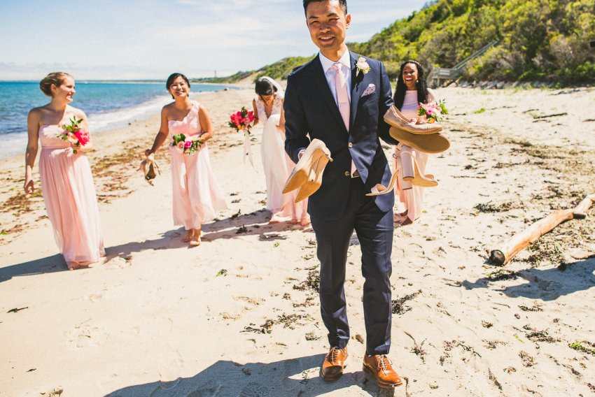 Groom holding bridesmaids shoes