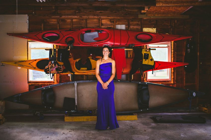 Bride in front of her kayaks at her home