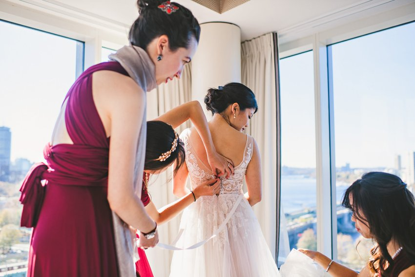 Bride putting on wedding dress at Liberty hotel