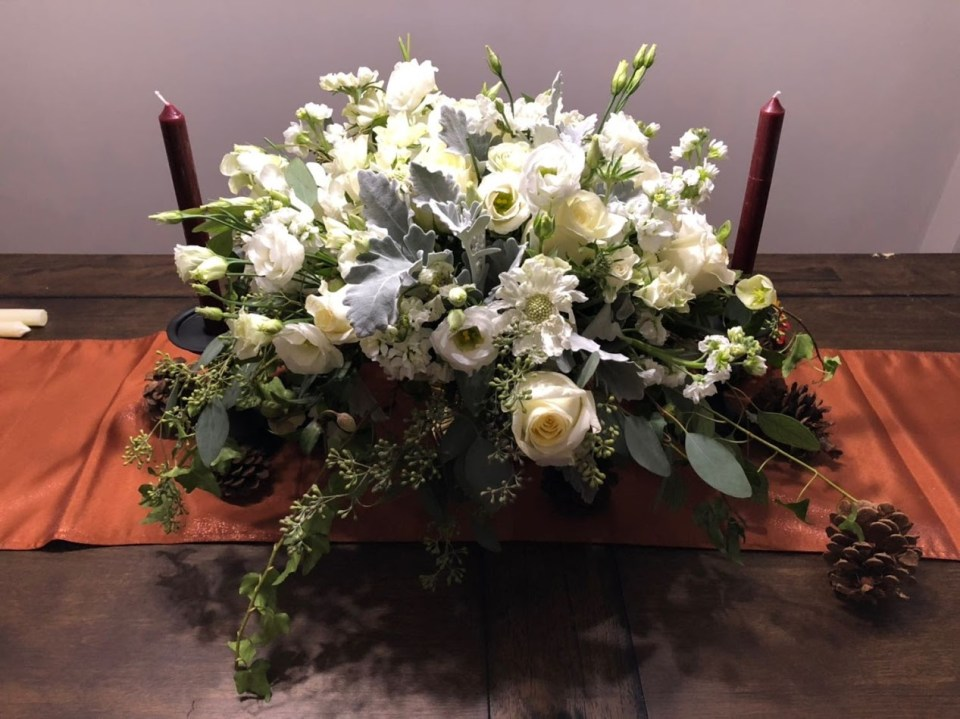 Centerpiece of Freindsgiving Tablescape including candles, flowers and table runner