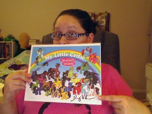 A webcomic photo of Alex holding up a print of a group of cartoon ponies that has been signed by Doug Walker.