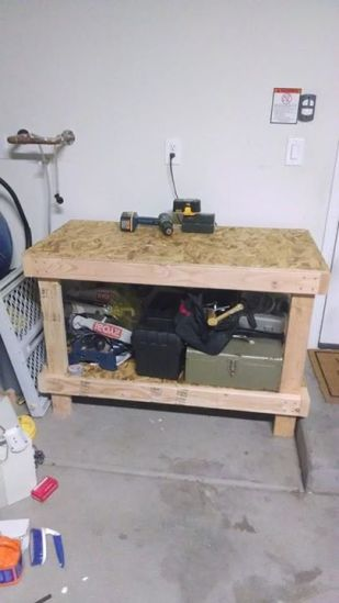 """I finally have a proper workbench in the garage...took about $45 in materials and about three hours to build. The frame is 2x4 screwed together; the top and the shelf underneath are 7/16"""" OSB."""