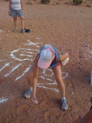 One of the hares puts down trail markings for chalk talk