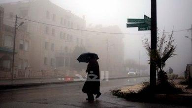 مواطن يتقي سقوط المطر بمظلة في أحد شوارع عمان خلال المنخفض الجوي الأخير-(الغد/ أرشيفية)