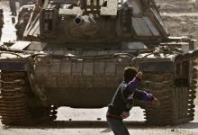 طفل فلسطيني يقف بمواجهة دبابة الاحتلال الاسرائيلي خلال االانتفاضة الفلسطينية