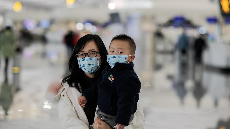 تعيرية لإمراة وطفلها يلبسان الكمامة للوقاية من فيروس كورونا