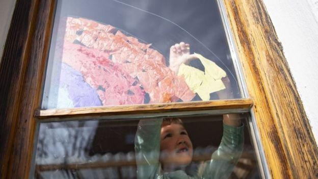 زين بعض الأطفال نوافذ بيوتهم برسوم لقوس قزح تعبيراً عن التفاؤل