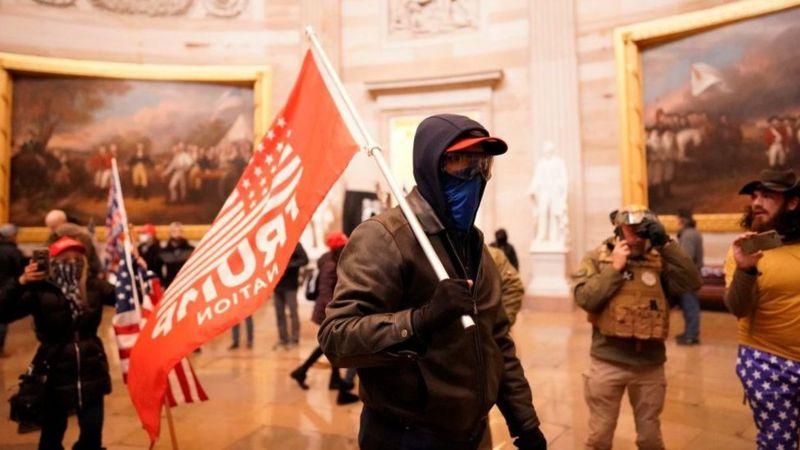 أحد المشاغبين يحمل علم ترامب داخل قاعة بالمبنى.