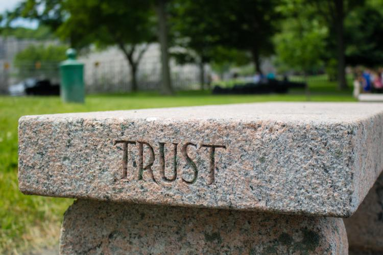 Trust engraved on gray stone bench