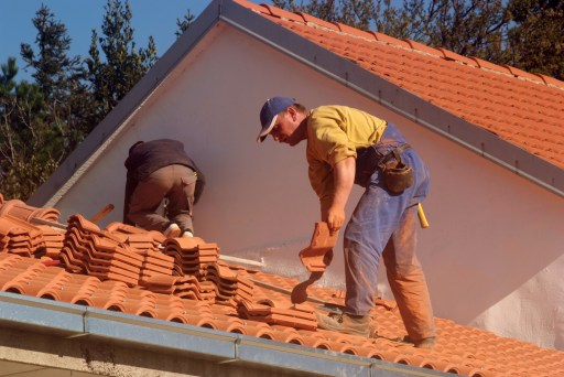 two roofers working on clay tile roof