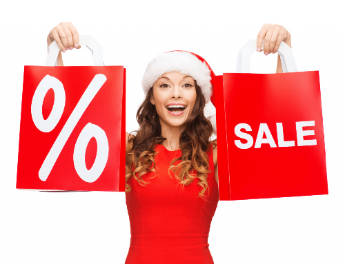 woman wearing santa hat holding up two red bags