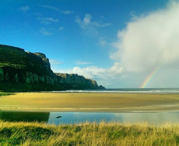 How to apply for a New Zealand Working Holiday Visa, South Island, Cliff, beach and rainbow over the ocean in The Catlins.