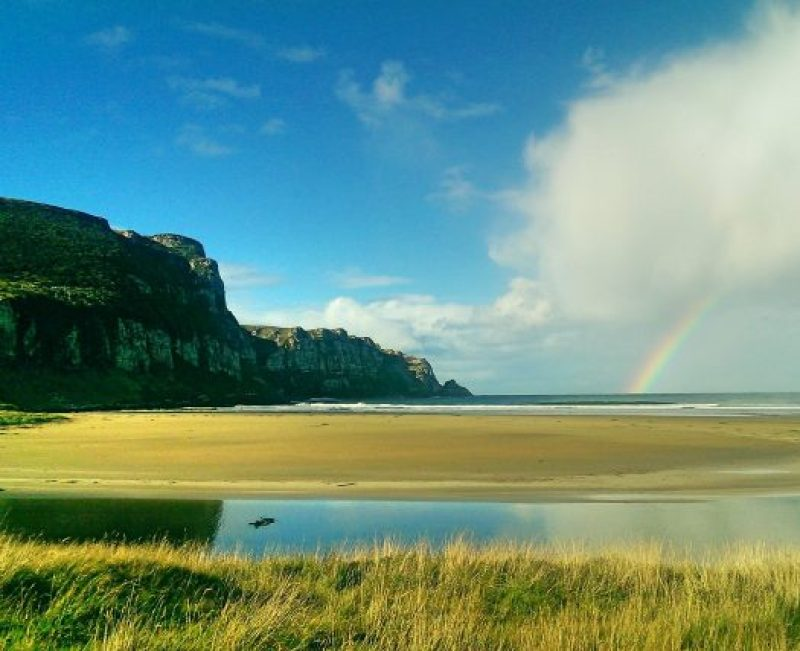 Cliff, beach and rainbow over the ocean in The Catlins.