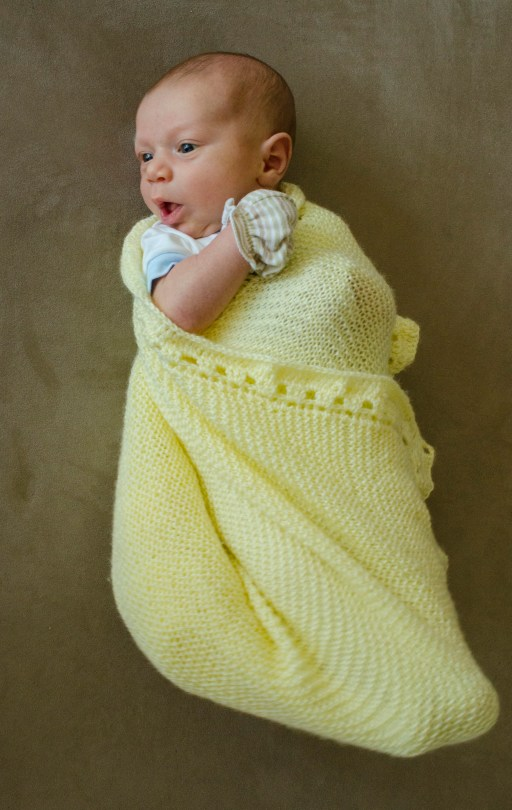 Kingsley wrapped in the blanket hand-knitted by neighbor Lena's mum Jeanette