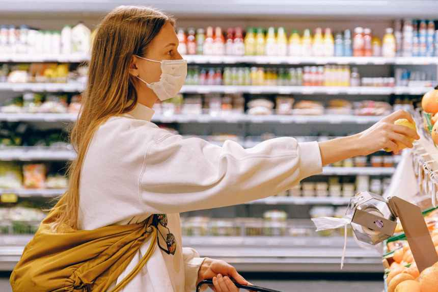 Woman wearing a facemask and shopping for groceries