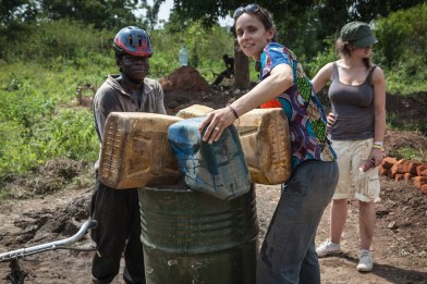 Kira helps pour water for cement mixing. 100litres of water delivered by a single bicycle.