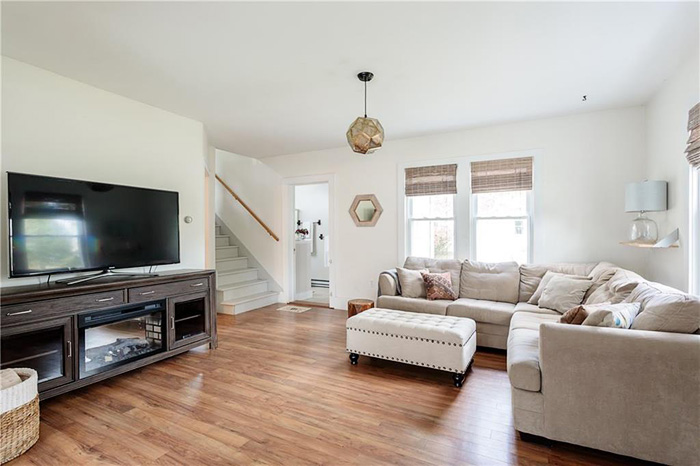 Living room with wood floors gray sectional couch and TV staged to sell