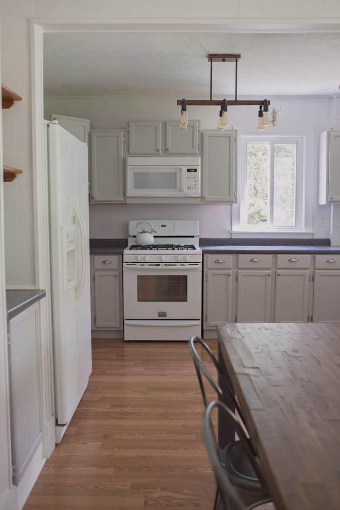 Farmhouse kitchen with painted gray cabinets and industrial pipe light fixture